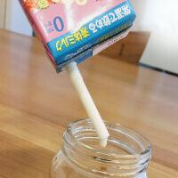 哺乳瓶に液体ミルクをストローで注ぐ